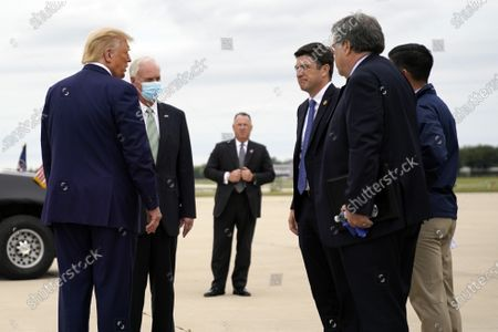 President Donald Trump talks with Sen. Ron Johnson, R-Wis., second from left, Attorney General William Barr, front right, and acting Homeland Security Secretary Chad Wolf, right, as he arrives at Waukegan National Airport in Waukegan, Ill., on his way to visit Kenosha, Wis., in Kenosha