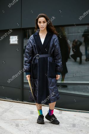 Adrianne Ho wears a deep purple puffer robe-style coat, green and hot pink mismatched socks, black sneakers, seen outside Sportmax show during Milan Fashion Week Womenswear Spring Summer 2020
