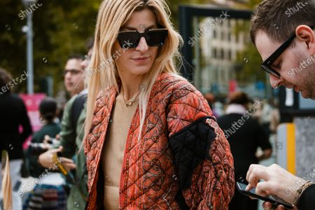 Ada Kokosar wears sunglasses, a necklace, a sand-color top, a paisley design quilted orange jacket, seen outside Sportmax show during Milan Fashion Week Womenswear Spring Summer 2020