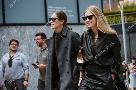 Darja Barannik wears mirror sunglasses, a gray wool jacket. Tine Andrea wears sunglasses, earrings, necklaces, a black leather shirt, a black leather skirt, a cow skin pattern handbag, seen outside Sportmax show during Milan Fashion Week Womenswear Spring Summer 2020
