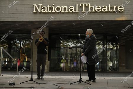 Actress and campaigner Vanessa Redgrave, listens as trumpeter Benjamin Amissah plays outside the National Theatre in London, . Vanessa Redgrave proposed that theatre people and theatre lovers should gather on the first of every month to appeal for support to raise funds to restore jobs across all the threatened arts sector and theatres, including the technical workers, across the UK