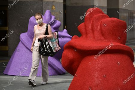 A woman walks past artist Lena Henkes sculptures, R.M.M. (Power Broker Purple) and R.M.M. (Organ, Organ, Organ Red)  at Rockefeller Center in New York. A special exhibition of site-specific works by artists Ghada Amer, Beatriz Cortez, Andy Goldsworthy, Lena Henke, Camille Henrot and Thaddeus Mosley comprises the second year of Frieze Sculpture at Rockefeller Center.