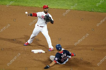 Philadelphia Phillies second baseman Jean Segura, left, throws to first after forcing out Washington Nationals' Juan Soto at second on a double play hit into by Howie Kendrick during the fifth inning of a baseball game, in Philadelphia