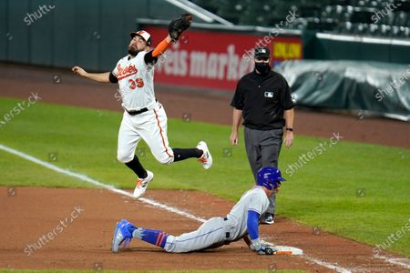 Baltimore Orioles first baseman Renato Nunez (39) reaches to catch a high throw from shortstop Andrew Velazquez, not visible, as New York Mets' Brandon Nimmo, bottom, slides back to first base on a line out by Michael Conforto during the seventh inning of a baseball game, in Baltimore. First base umpire Chris Conroy looks on