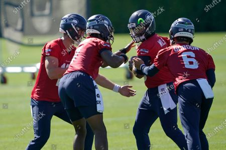 Seattle Seahawks starting quarterback Russell Wilson, second from right, runs a drill where his backup quarterbacks, Danny Etling, left, Geno Smith, second from left, and Anthony Gordon (6) make motions to strip the ball from him during NFL football training camp, in Renton, Wash