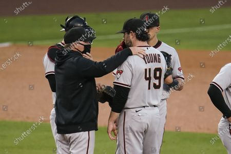 Arizona Diamondbacks pitching coach Matt Herges, left, talks to starting pitcher Alex Young during the first inning of the team's baseball game against the Los Angeles Dodgers, in Los Angeles