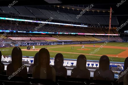 Cardboard cutouts of fans decorate the stands as Arizona Diamondbacks starter Alex Young pitches to Los Angeles Dodgers' Max Muncy during the fifth inning of a baseball game, in Los Angeles