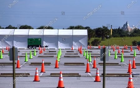 Traffic cones are seen in a parking lot at a nearly empty COVID-19 testing site operated by the Florida Division of Emergency Management.  As the number of coronavirus cases in Florida has dropped in recent weeks, so has the demand for testing. The Expedition Everest roller coaster at Walt Disney World's Animal Kingdom can be seen in the distance.