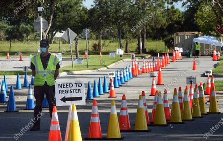 A worker waits to direct cars at a nearly empty COVID-19 testing site operated by the Florida Division of Emergency Management near Walt Disney World. As the number of coronavirus cases in Florida has dropped in recent weeks, so has the demand for testing.