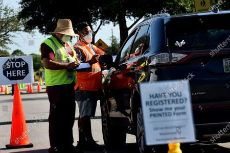Workers greet people in a car at a nearly empty COVID-19 testing site operated by the Florida Division of Emergency Management near Walt Disney World. As the number of coronavirus cases in Florida has dropped in recent weeks, so has the demand for testing.