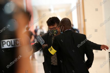 Dr. Patrick Pelloux, who arrived shortly after the shooting at satirical newspaper Charlie Hebdo, is checked for security outside the courtroom during the opening of the 2015 attacks trial, in Paris. Thirteen men and a woman go on trial Wednesday over the 2015 attacks against a satirical newspaper and a kosher supermarket in Paris that marked the beginning of a wave of violence by the Islamic State group in Europe. Seventeen people and all three gunmen died during the three days of attacks in January 2015
