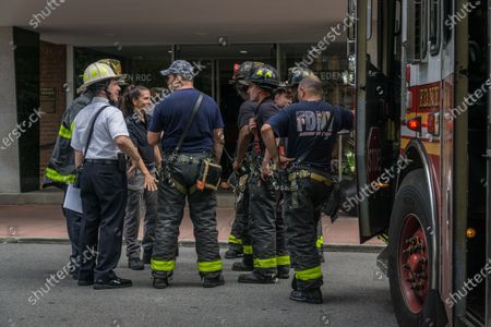 Stock Image of Multiple fire engines respond to a fire in a high rise residential building in Harlem. Later New York City Fire Department Commissioner Daniel Nogro held a press conference to congratulate fire fighter Brian Quinn from Ladder Company 30 on a heroic rescue of a woman hanging out of her 16th floor window.