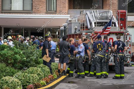 Stock Photo of Multiple fire engines respond to a fire in a high rise residential building in Harlem. Later New York City Fire Department Commissioner Daniel Nogro held a press conference to congratulate fire fighter Brian Quinn from Ladder Company 30 on a heroic rescue of a woman hanging out of her 16th floor window.