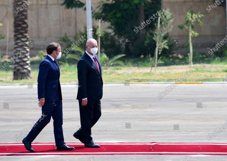 Iraqi President Barham Salih (R) and French President Emmanuel Macron (L) review honor guards during a welcoming ceremony at the presidential palace in Baghdad, Iraq, 02 September 2020. Macron arrived in Iraq's capital city Baghdad on his first official visit to the country.