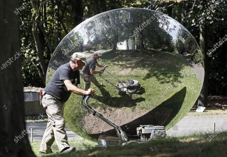 Gardener at work mirrors in an artwork by British Indian artist Anish Kapoor on a sunny day at the sculpture museum set in nature in Cologne, Germany