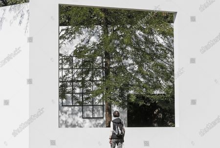 Stock Image of Woman watches into the garden gallery artwork by Japanese architect Sou Fujimoto on a sunny day at the sculpture museum set in nature in Cologne, Germany