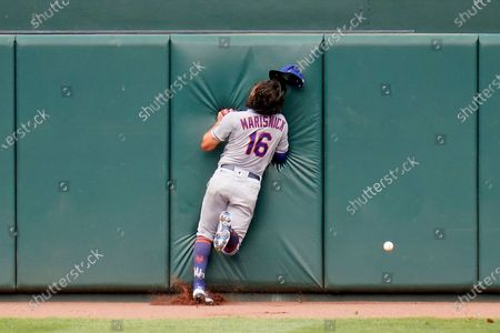 New York Mets center fielder Jake Marisnick smashes into the center field wall while chasing a triple by Baltimore Orioles' Pedro Severino during the second inning of a baseball game, in Baltimore
