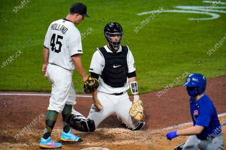 Pittsburgh Pirates relief pitcher Derek Holland (45) and catcher Kevin Stallings collect themselves after an error by shortstop Kevin Newman allowed two runs to score during the eighth inning of a baseball game in Pittsburgh, . The Cubs won 8-2