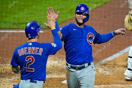 Chicago Cubs' Willson Contreras, right, and Nico Hoerner celebrate after both scored on a single by Anthony Rizzo off Pittsburgh Pirates relief pitcher Derek Holland during the seventh inning of a baseball game in Pittsburgh, . The Cubs won 8-2