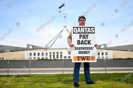 A Qantas employee holds a sign during a rally organised by the Transport Workers Union (TWU) outside Parliament in Canberra, Australia, 03 September 2020. Qantas has announced that it will slash over 2400 jobs, prompting unions to call on the federal government to intervene