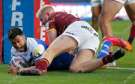 Dominique Peyroux of St Helens goes over for the 8th try with Oliver Wilson of Huddersfield Giants on top