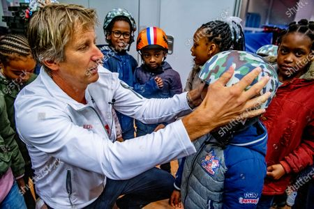 Stock Image of Edwin van der Sar hands out bicycle helmets to pupils of the Blue Line Primary School as part of the Safe cycling to school project, a project set up by the Edwin van der Sar Foundation and the ANWB to reduce the number of road casualties.