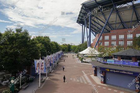 Event staff walk the mostly empty grounds of the Billie Jean King National Tennis Center during the second round of the US Open tennis championships, in New York