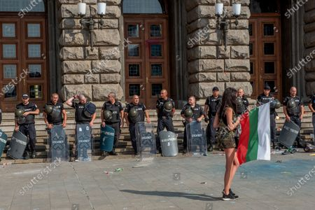 Riot police stand on guard facing off with a female protester during the demonstration. For the 56th consecutive day, Bulgarians have gathered outside government buildings accusing the Prime Minister, Boyko Borisov of corruption and protecting powerful tycoons. Demonstrators in the capital and cities across the country are calling for the resignation of the Prime Minister and his centre-right government.