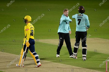 Gareth Batty and Ben Foakes of Surrey celebrate the wicket of Lewis McManus