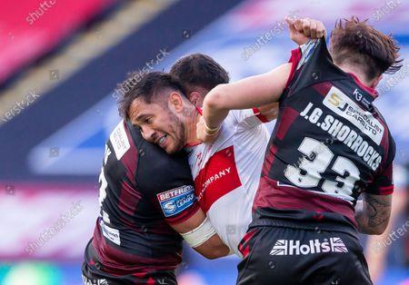 Hull KR's Nathaniel Peteru is tackled by Wigan's Mitch Clarke & Joseph Shorrocks.