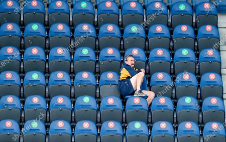 Stock Picture of Hull KR coach Tony Smith sits alone in the stands watching as his side demolish Wigan 34-18.