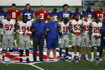 New York Giants head coach Joe Judge, center, stands with arms linked with his players to make a social injustice statement prior to their scrimmage at the NFL football team's training camp in East Rutherford, N.J., . A long-time advocate of the right to protest for social change and equality, New York Giants co-owner John Mara admits he was stunned listening to his players talk about their experiences with police and authorities in the wake of the death George Floyd in June