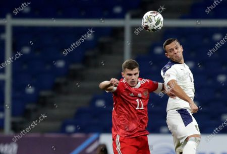 Russia's Roman Zobnin, left, jumps for the ball with Serbia's Nemanja Maksimovic during the UEFA Nations League soccer match between Russia and Serbia at the VTB Arena, in Moscow, Russia