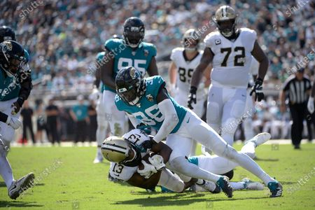 New Orleans Saints wide receiver Michael Thomas (13) is tackled by Jacksonville Jaguars cornerback A.J. Bouye (21) and defensive back Ronnie Harrison (36) after catching a pass during the second half of an NFL football game, in Jacksonville, Fla. The Cleveland Browns have acquired safety Ronnie Harrison in a trade with the Jacksonville Jaguars, who will receive a fifth-round pick in 2021 from Cleveland. The loss of rookie safety Grant Delpit for the season with a torn Achilles tendon sent the Browns shopping for a safety. On Thursday, Sept. 3, 2020, general manager Andrew Berry pulled off the swap for Harrison, who is in his third season from Alabama