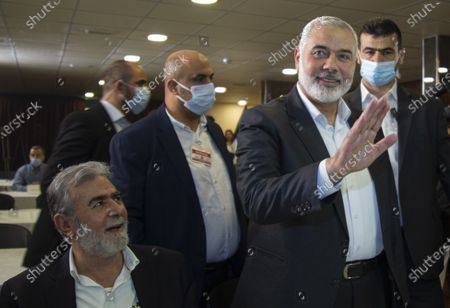 Palestinian top leader of the Hamas movement, Sheikh Ismail Haniyeh (R) and the top leader of the Islamic Jihad, Zaid Nakhaleh (L), and their accompanying delegation, with other Palestinian leaders attend the opening session of the meeting of the general secretaries of the Palestinian national action factions, with the Palestinian president Mahmoud Abbass who speaks via video conference from the West Bank in occupied Palestine, at the invitation of the Embassy of the State of Palestine, in the hall of the martyr President Yasser Arafat, at the embassy in Beirut, Lebanon 03 September 2020.