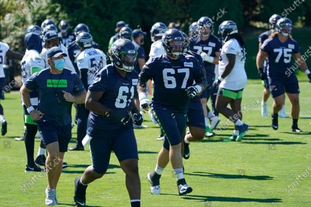 Seattle Seahawks centers Kyle Fuller (61) and B.J. Finney (67) run after stretching during NFL football training camp, in Renton, Wash
