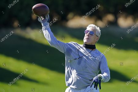 Seattle Seahawks head coach Pete Carroll passes the football during NFL football training camp, in Renton, Wash