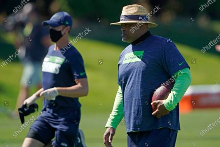 Stock Image of Seattle Seahawks defensive coordinator Ken Norton, Jr. holds a football during NFL football training camp, in Renton, Wash