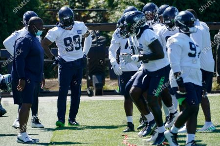 Seattle Seahawks defensive end Damontre Moore (99) stands with teammates during NFL football training camp, in Renton, Wash