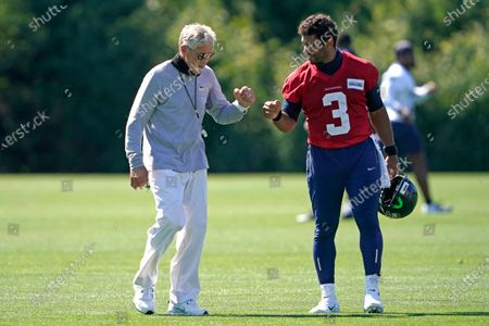 Seattle Seahawks quarterback Russell Wilson (3) bumps fists with head coach Pete Carroll after the last day of NFL football training camp, in Renton, Wash