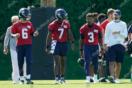 Seattle Seahawks quarterbacks Russell Wilson (3), Geno Smith (7) and Anthony Gordon (6) walk with offensive coordinator Brian Schottenheimer, right, and head coach Pete Carroll, left, following the last day of NFL football training camp, in Renton, Wash