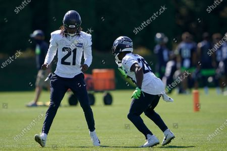 Seattle Seahawks cornerback Tre Flowers (21) and safety Ugo Amadi, right, gets some extra steps in at the end of NFL football training camp, in Renton, Wash