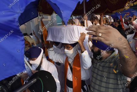 """Members of the Sikh community, receive Sikh religious items brought in from Afghanistan, alongwith more than a hundred Sikh Afghans and Hindus who've reached India from Kabul, fleeing religious prosecution, at Indira Gandhi International IGI Airport Terminal 3 on September 3, 2020 in New Delhi, India. A batch of 180 Sikh families from Afghanistan arrived here on Thursday on long-term visas, Delhi Sikh Gurdwara Management Committee president Manjinder Singh Sirsa said. Following an attack on a gurdwara in Afghanistan in March this year, there has been an """"exodus"""" of Sikh and Hindu families. Till date more than 450 families have already arrived in Delhi."""