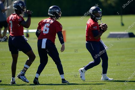 Seattle Seahawks quarterback Russell Wilson, right, with backup quarterbacks Anthony Gordon (6) and Geno Smith (7) during NFL football training camp, in Renton, Wash