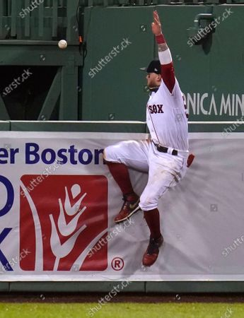Boston Red Sox right fielder Alex Verdugo slams into the bullpen wall while chasing a three-run home by Toronto Blue Jays' Teoscar Hernandez, which broke a 2-2 tie, during the 10th inning of a baseball game, in Boston