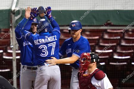 Toronto Blue Jays' Teoscar Hernandez (37) is congratulated by Cavan Biggio, left, and Derek Fisher after his three-run home run, breaking a 2-2 tie, in 10th inning of the team's baseball game against the Boston Red Sox, in Boston. At lower right is Boston Red Sox catcher Christian Vazquez