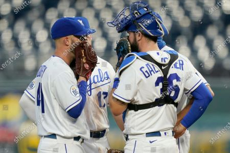 Kansas City Royals starting pitcher Danny Duffy, left, holds a mound meeting with catcher Cam Gallagher (36) and others after giving up a run in the second inning of the team's baseball game against the Chicago White Sox at Kauffman Stadium in Kansas City, Mo