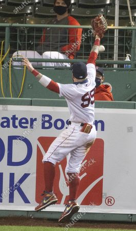 Stock Image of Boston Red Sox center fielder Alex Verdugo is unable to stop the ball for a home run by Toronto Blue Jays designated hitter Teoscar Hernandez during the tenth inning of the MLB baseball game between the the Toronto Blue Jays and Boston Red Sox at Fenway Park in Boston, Massachusetts, USA, 03 September 2020.