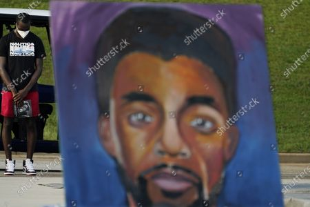 Man prays behind a painting of Chadwick Boseman during a tribute to Boseman's life, in Anderson, S.C
