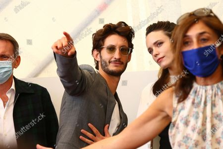 Benoit Magimel points something out to Stacy Martin at the photo call for the film 'Amants (Lovers)' during the 77th edition of the Venice Film Festival in Venice, Italy
